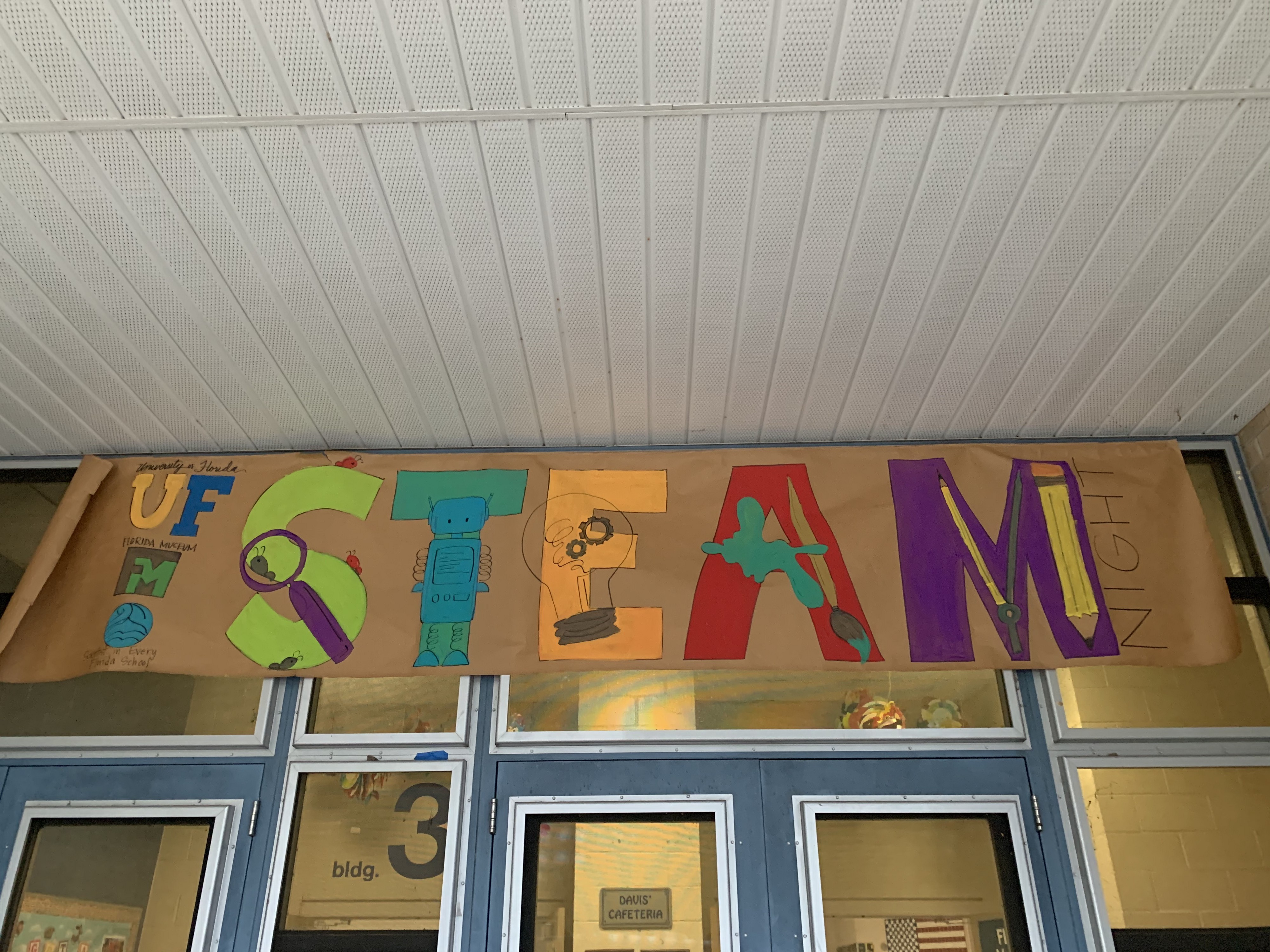 A brown poster with the words STEAM Night. Hosted by UF, Florida Museum, & TESI